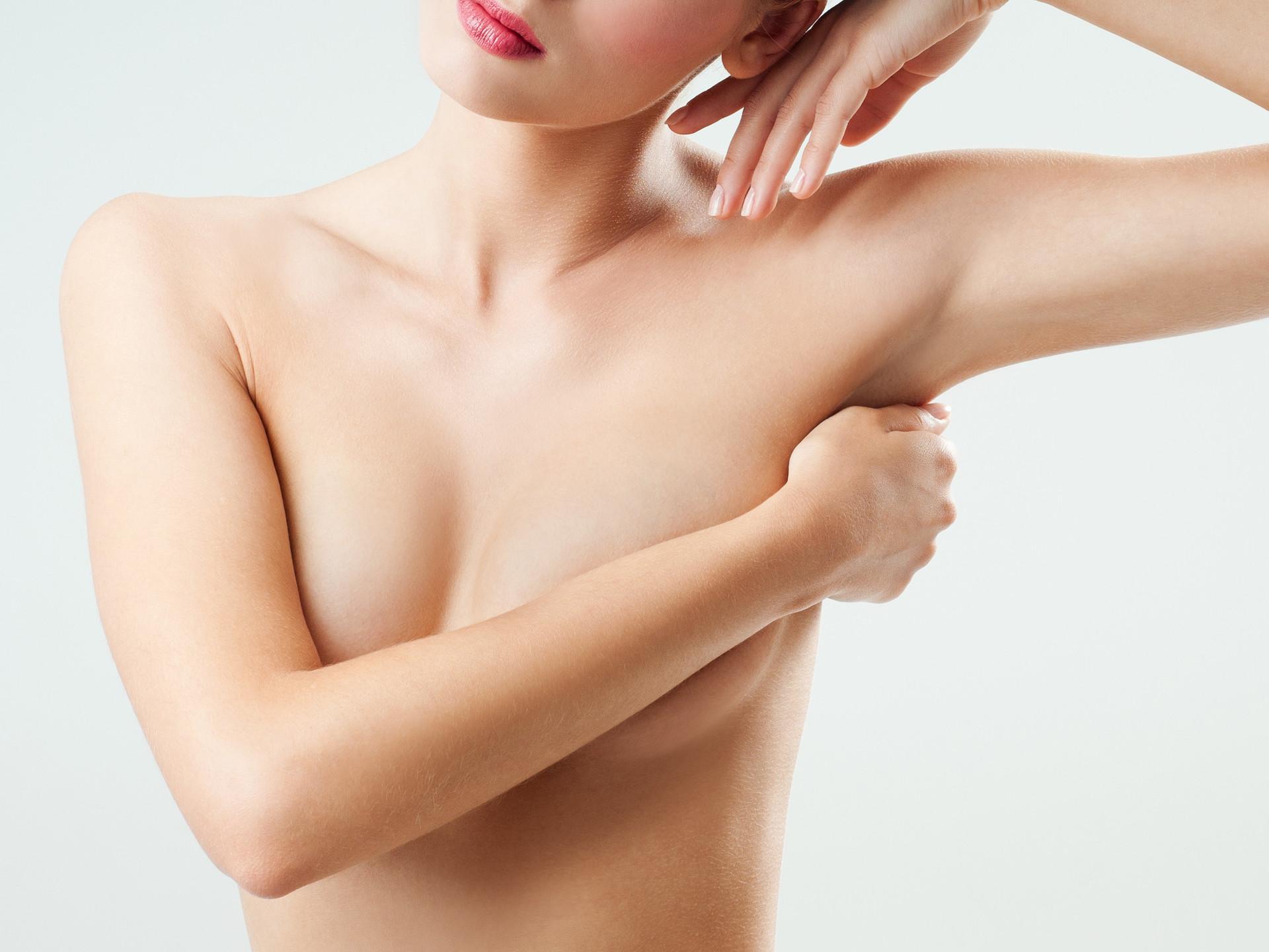 Frau verdeckt nackte Brust mit Arm